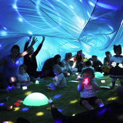 Image of toddlers and parents underneath parachute with fun lights