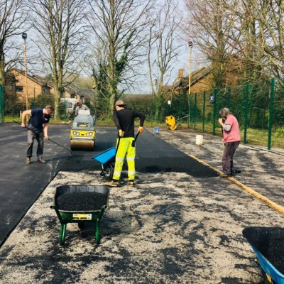 Image of workmen laying tarmac on the court